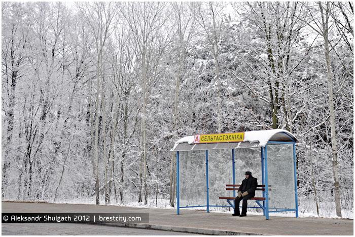 Мужчина сидит на остановке в ожидании общественного транспорта