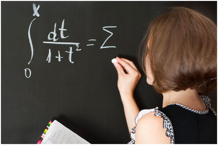 Учитель в школе у доски пишет мелом