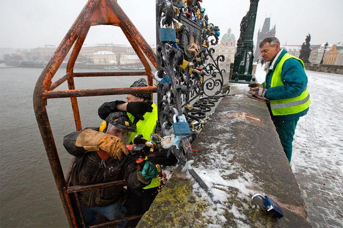 Карлов Мост в Праге. Бригада рабочих спиливает свадебные замки.