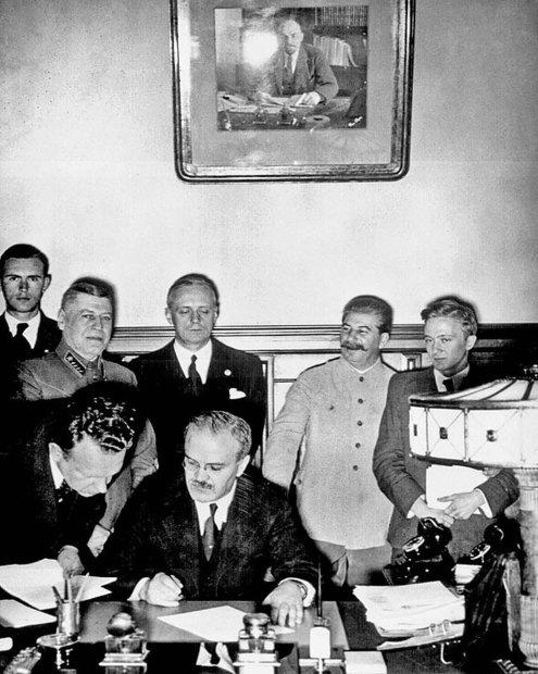 Молотов подписывает советско-германский договор. За его спиной министр иностранных дел Германии Иоахим фон Риббентроп и Иосиф Сталин