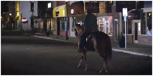 Человек на коне едет по городу